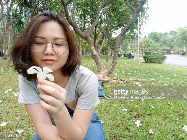 Woman Looking At Flower In Park
