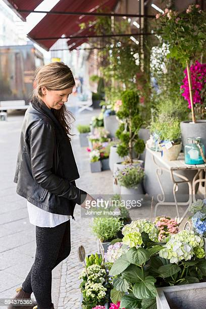 Woman looking at flowers in flower shop