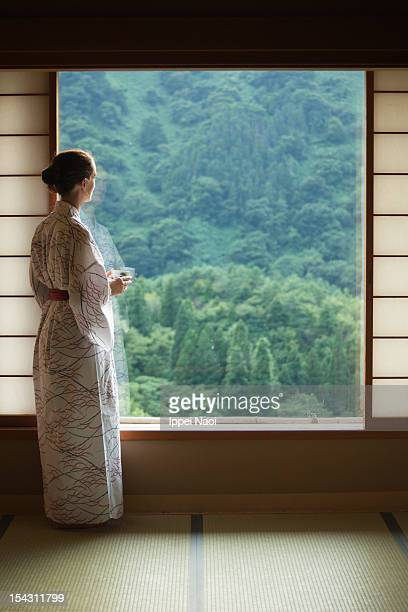 Woman looking at forest from Japanese room