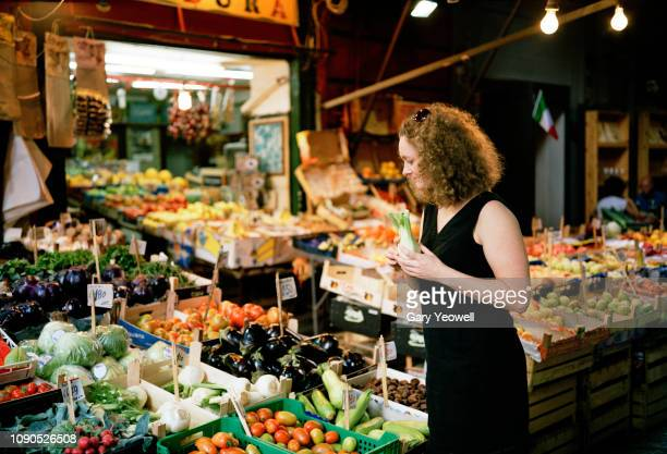 woman looking at fresh produce stall in palermo - markt stockfoto's en -beelden