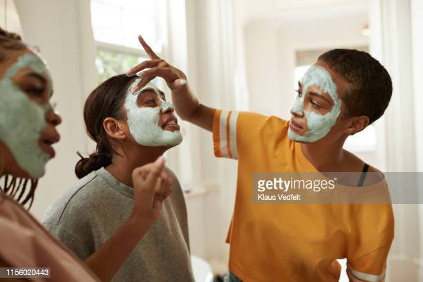 woman looking at friend spreading cream with fingers - female friendship stock pictures, royalty-free photos & images