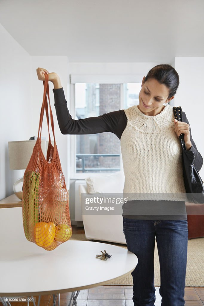 Woman looking at fruits in netting bag : Stockfoto