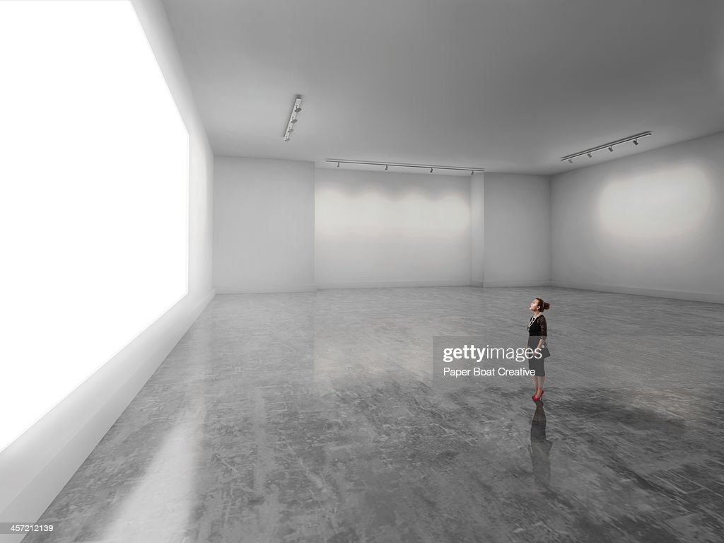 Woman looking at giant glowing white screen : ストックフォト