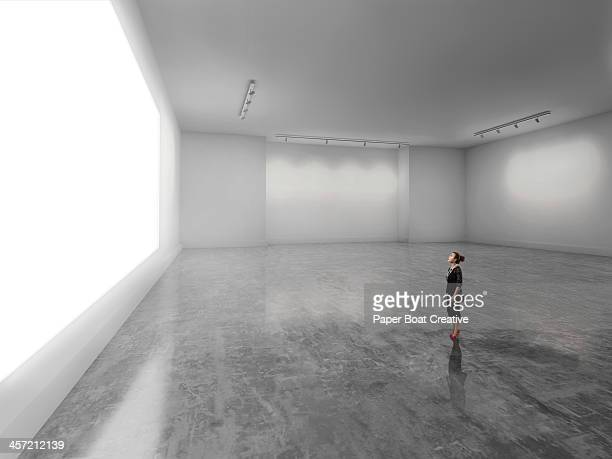 woman looking at giant glowing white screen - 展覧会 ストックフォトと画像