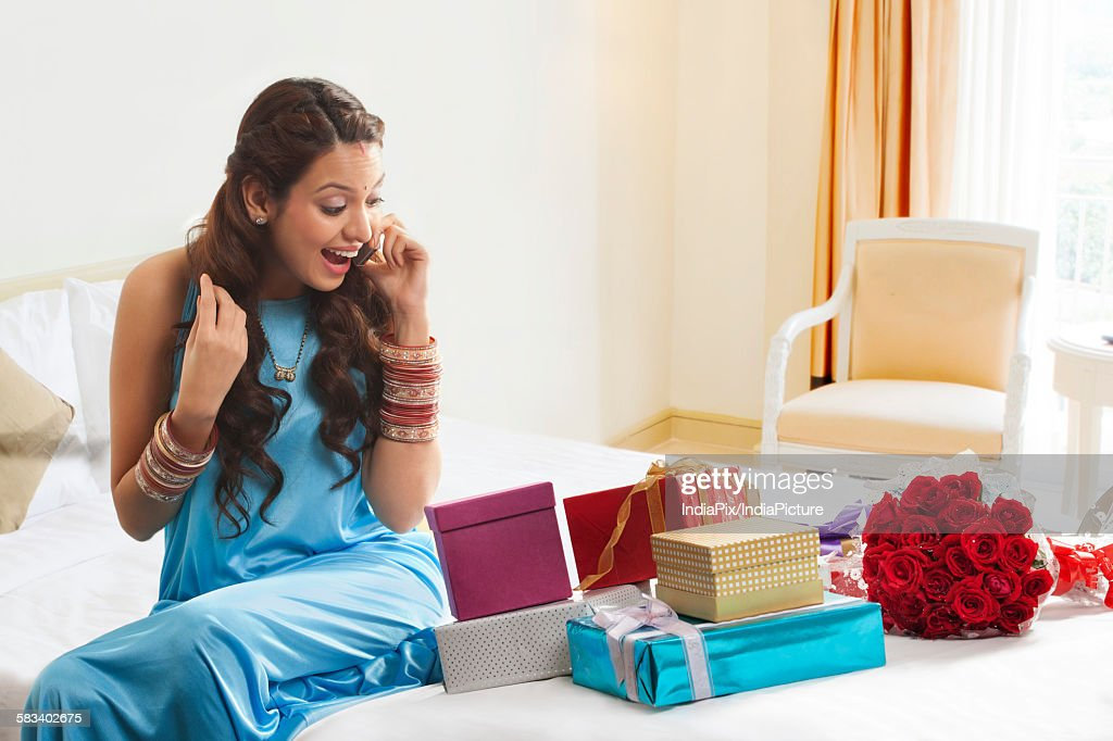 Woman looking at gifts while talking on mobile phone : Stock Photo
