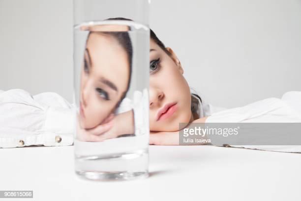 woman looking at glass of water - durst stock-fotos und bilder