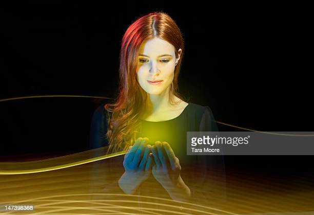 woman looking at glowing mobile with light trails - light trail stock pictures, royalty-free photos & images