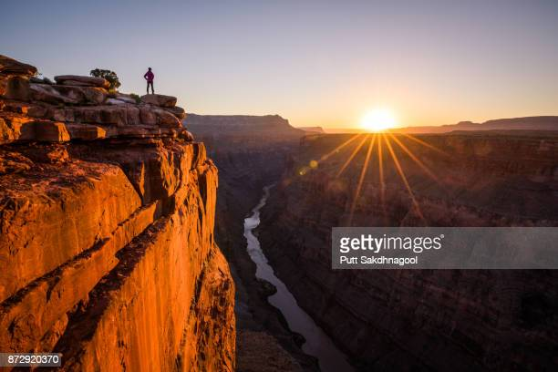 a woman looking at grand canyon and colorado river from toroweap overlook at sunrise - category:grand_canyon_national_park stock pictures, royalty-free photos & images