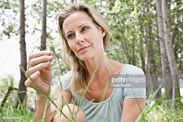 woman looking at grass in forest - graspflanze stock-fotos und bilder
