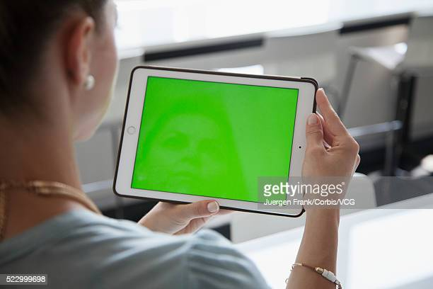 Woman looking at green screen on her tablet