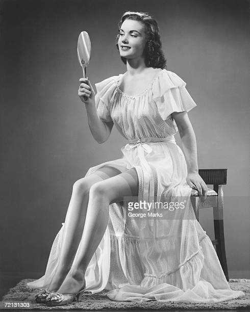 woman looking at hand mirror (b&w) - women in slips stock photos and pictures