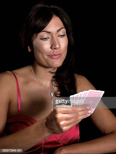 Woman looking at hand of playing cards