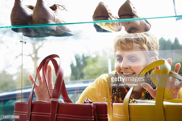 Woman looking at handbags in boutique window