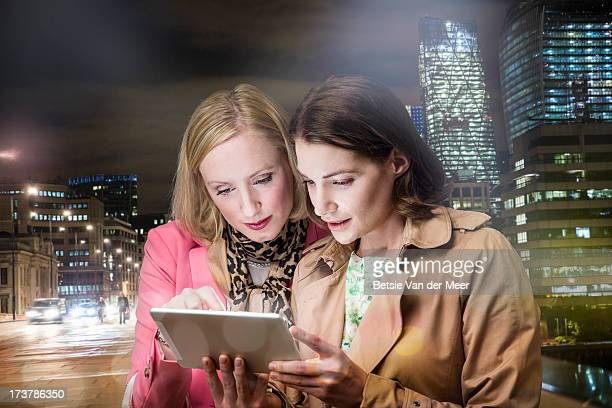 Woman looking at handheld computer in city.
