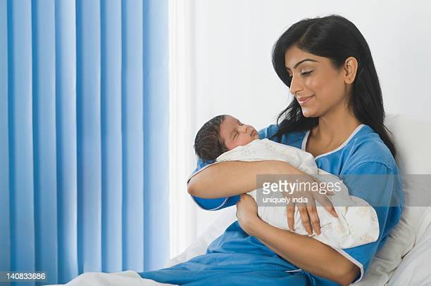 Woman looking at her baby on the bed