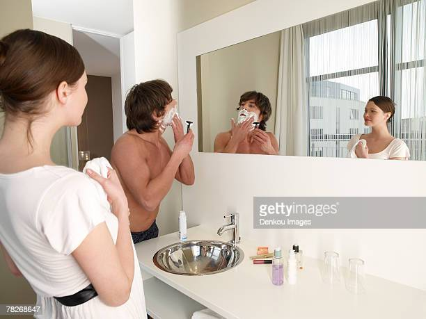 Woman looking at her boyfriend shaving.
