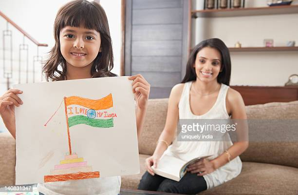 Woman looking at her daughter showing drawing of Indian flag