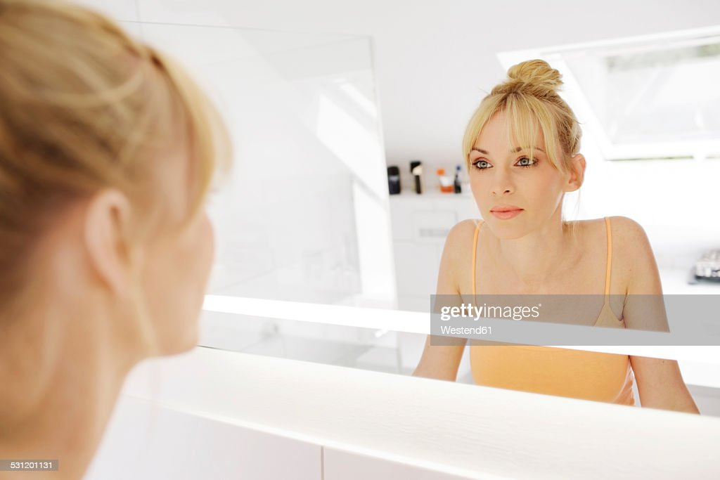 Woman looking at her mirror image in the bathroom : Stock Photo