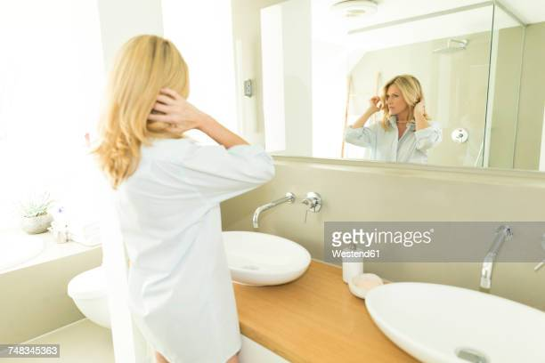 woman looking at her mirror image in the bathroom - one mature woman only stock pictures, royalty-free photos & images