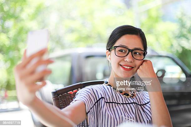 woman looking at her mobile phone with smile - short sleeved stock pictures, royalty-free photos & images