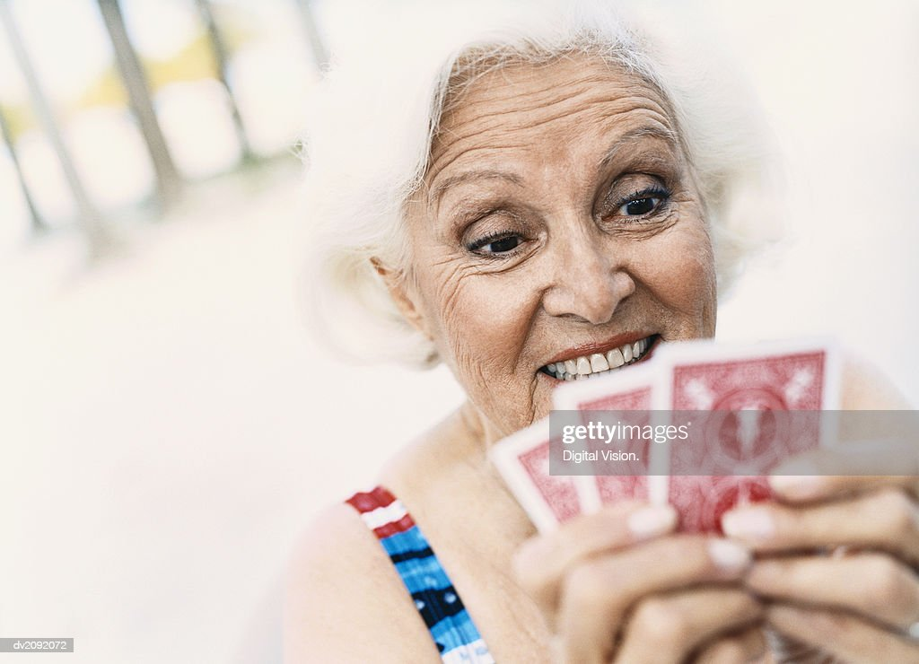 Woman Looking at Her Playing Cards : Stock Photo