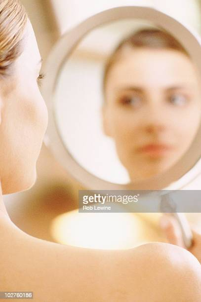 woman looking at her reflection in a mirror - vanity mirror stock photos and pictures