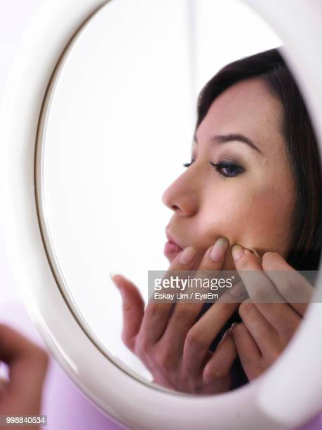 Woman Looking At Her Reflection In Mirror At Home