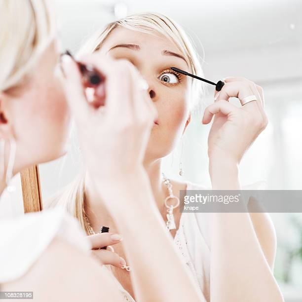 Woman looking at herself in a mirror applying mascara
