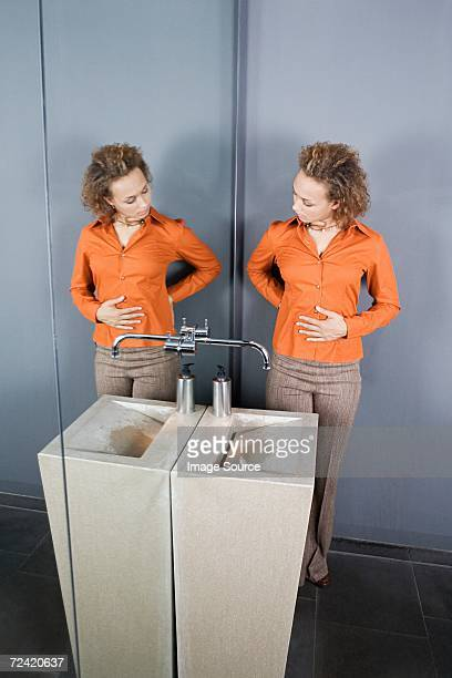 Frau blickt auf sich selbst im Spiegel