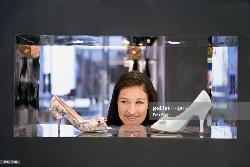 Woman looking at high heel shoes : Stock Photo
