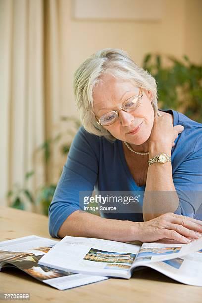 Woman looking at holiday brochures