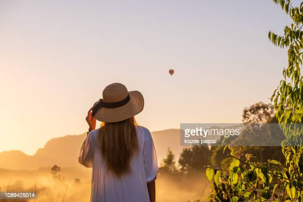 woman looking at hot air balloon in Laos during foggy sunset .