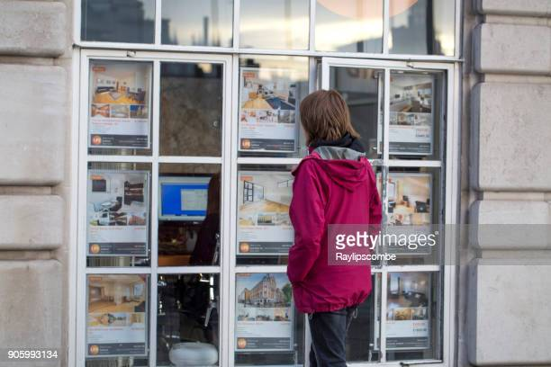 woman looking at houses and flats in the window of an estate agent in london, uk - house rental stock photos and pictures