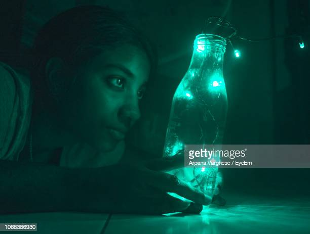 woman looking at illuminated lights in bottle at home - 18 19 years stock pictures, royalty-free photos & images