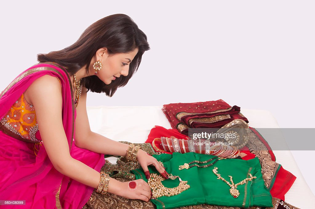 Woman looking at jewelery and wedding attire : Stock Photo