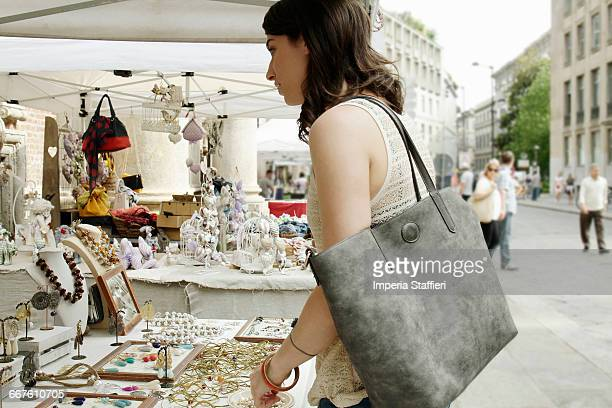 Woman looking at jewellery on market stall, Milan, Italy
