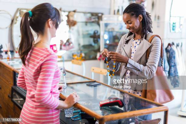 woman looking at jewelry in clothes shop - afro caribbean ethnicity stock pictures, royalty-free photos & images