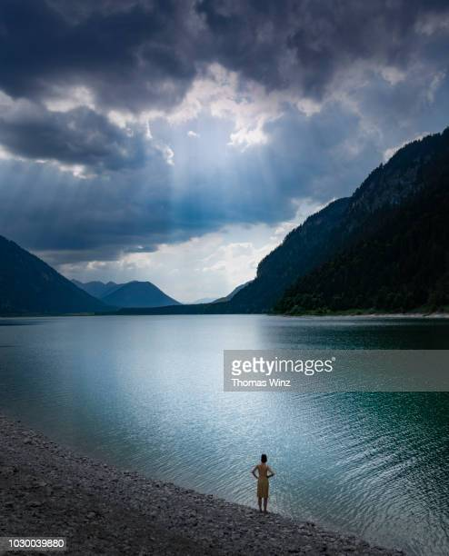 woman looking at lake , cloudscape and mountain - nature stock pictures, royalty-free photos & images