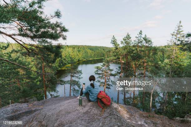 woman looking at lake in finland and drinking tea - finland stock pictures, royalty-free photos & images