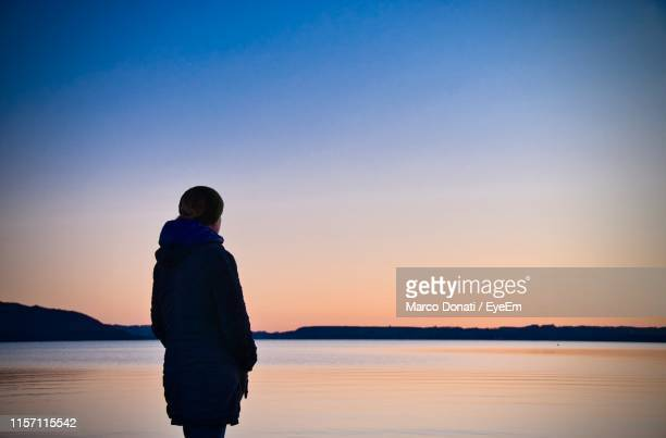 woman looking at lake while standing against clear sky during sunset - rotorua stock pictures, royalty-free photos & images