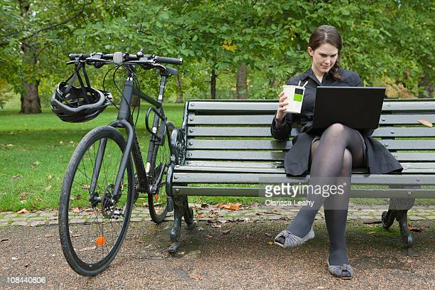 Woman looking at laptop and eating lunch