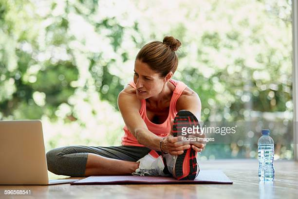 Woman looking at laptop while exercising at gym