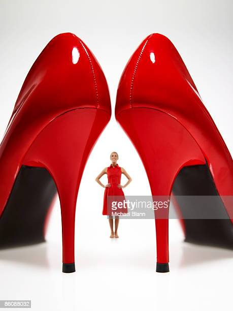 woman looking at large red heels - high heels stock pictures, royalty-free photos & images