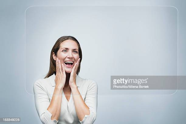 Woman looking at large transparent touch screen with surprised expression on face