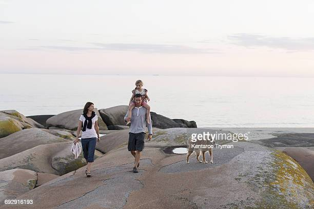 Woman looking at man carrying girl on shoulder walking against sky