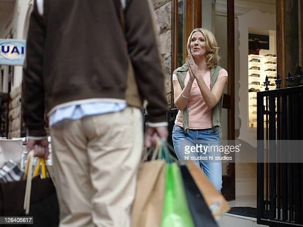 woman looking at man carrying shopping bags - fanny pic stock photos and pictures