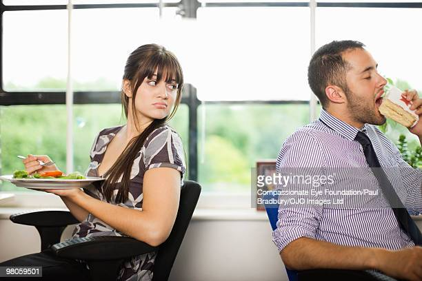 """woman looking at man eating large piece of cake - """"compassionate eye"""" stock pictures, royalty-free photos & images"""