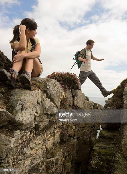 woman looking at man jumping through crack in cliff top - legs apart stock pictures, royalty-free photos & images