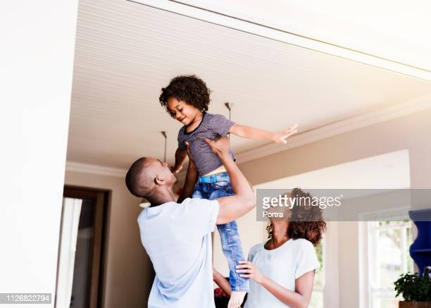 Woman looking at man lifting son in house