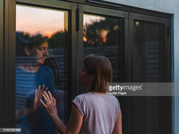 woman looking at man quarantined behind glass door - photographed through window stock pictures, royalty-free photos & images
